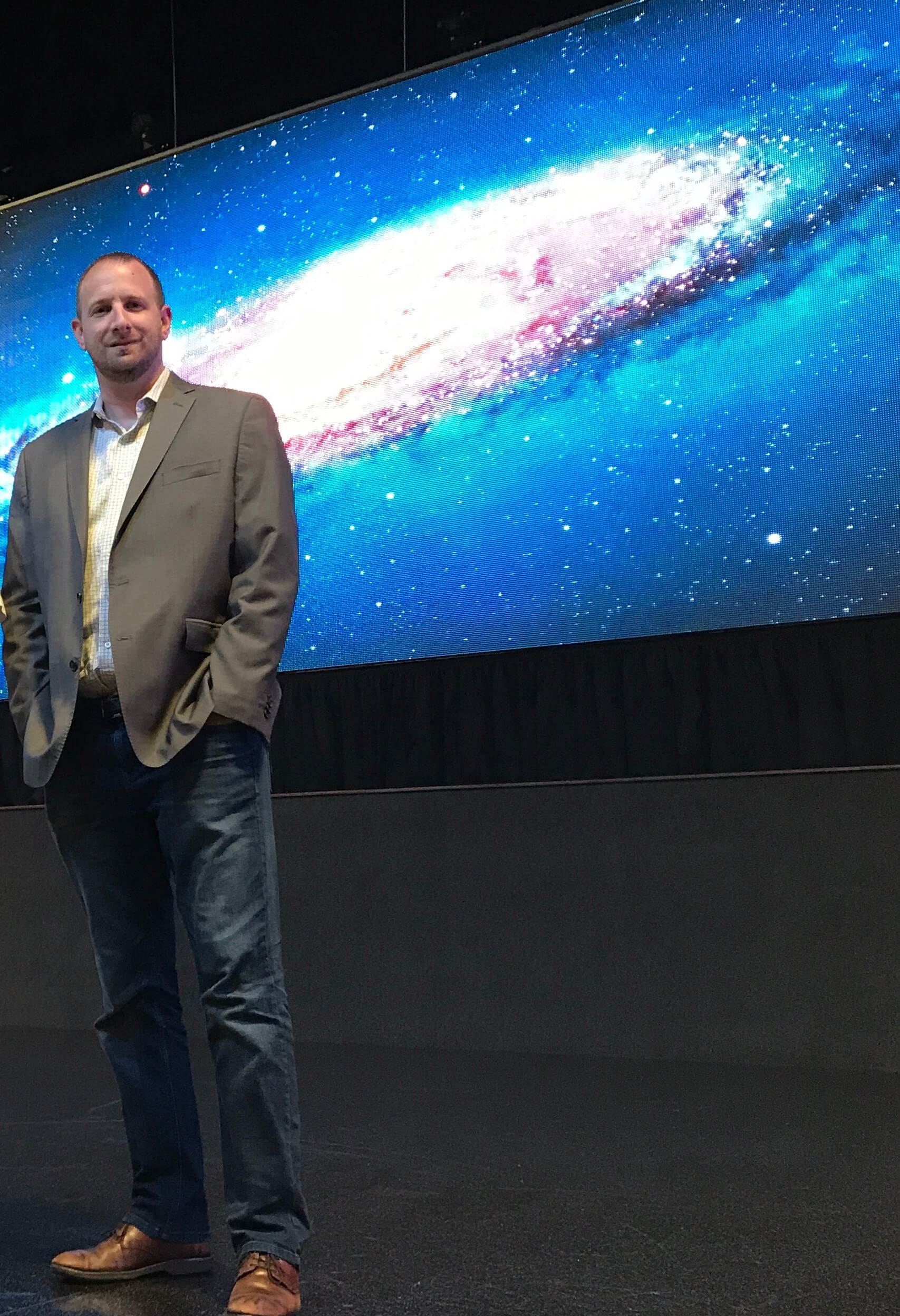 IAS Technology CEO Jeremy Caldera stands in front of a Delta Displays LED video wall similar to the one he is installing for a Fortune 100 company.